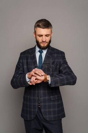 Photo for Handsome bearded businessman in suit looking at wristwatch on grey background - Royalty Free Image
