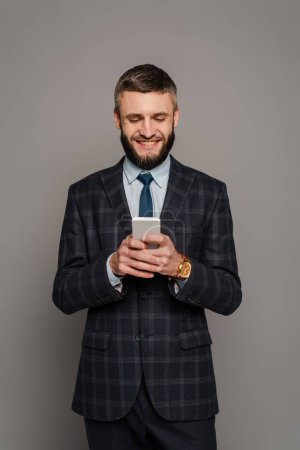 Photo for Happy handsome bearded businessman in suit using smartphone on grey background - Royalty Free Image
