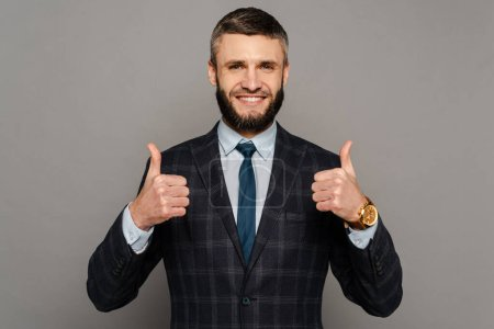 happy handsome bearded businessman in suit showing thumbs up on grey background