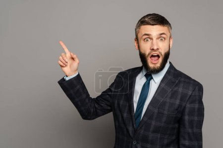 Photo for Excited bearded businessman in suit pointing with finger on grey background - Royalty Free Image