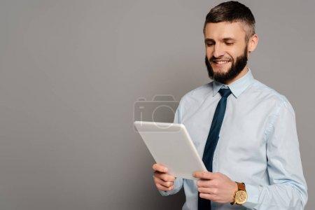 Lächelnder gutaussehender bärtiger Geschäftsmann mit digitalem Tablet auf grauem Hintergrund