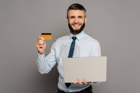 smiling handsome bearded businessman with laptop and credit card on grey background