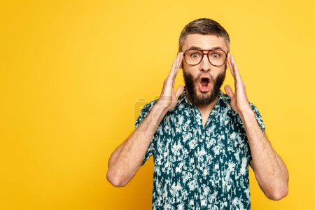 Photo for Shocked bearded guy in glasses with open mouth touching head on yellow - Royalty Free Image