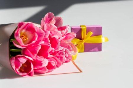 Photo pour Bouquet de tulipes roses près de petite boîte cadeau sur blanc, concept de fête des mères - image libre de droit