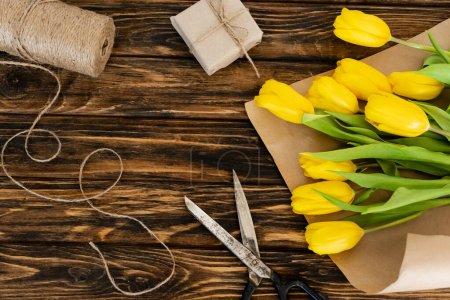 widok z góry żółte tulipany w pobliżu nożyczek, jutowy sznurek liny i pudełko na prezent na drewnianej powierzchni, koncepcja dzień matki