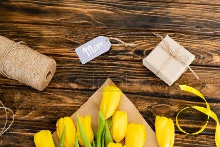 Photo pour Vue du dessus des tulipes jaunes près de corde de ficelle de jute et boîte cadeau avec lettrage maman sur l'étiquette, concept de fête des mères - image libre de droit