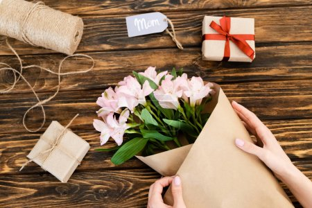 Photo for Cropped view of woman wrapping pink flowers in paper near gift boxes on wooden surface, mothers day concept - Royalty Free Image