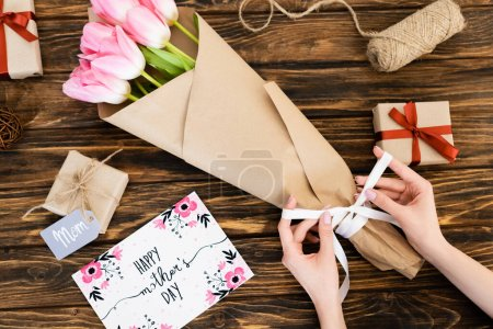 Photo for Cropped view of woman touching ribbon on wrapped in paper pink tulips near greeting card with happy mothers day lettering and gift boxes on wooden surface - Royalty Free Image