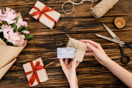 Photo pour Vue recadrée de la femme tenant boîte cadeau avec lettrage maman sur étiquette près de fleurs roses enveloppées dans du papier sur la surface en bois, concept de fête des mères - image libre de droit