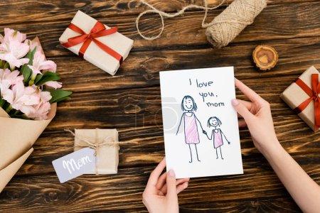 Photo pour Vue recadrée de la femme tenant la carte de vœux avec je t'aime maman lettrage près de cadeaux et fleurs sur la surface en bois - image libre de droit
