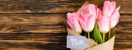 Photo pour Plan panoramique de tag avec lettrage maman sur des tulipes roses enveloppées dans du papier sur une surface en bois, concept de fête des mères - image libre de droit