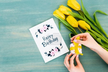 Photo for Cropped view of woman holding gift box near greeting card with happy birthday lettering and yellow tulips on blue wooden surface - Royalty Free Image