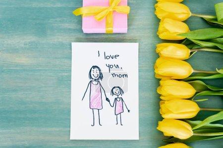 Photo pour Vue du dessus de la petite boîte cadeau près de la carte de vœux avec je t'aime maman lettrage et tulipes jaunes sur la surface en bois bleu - image libre de droit