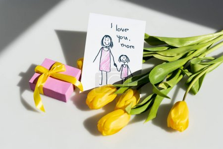Photo for Sunlight on yellow tulips near gift box and greeting card with i love you mom lettering on white, mothers day concept - Royalty Free Image