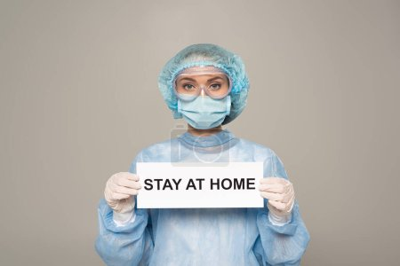 Photo for Doctor in protective googles and medical mask holding card with stay at home lettering isolated on grey - Royalty Free Image
