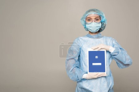 Photo for KYIV, UKRAINE - APRIL 1, 2020: Doctor in safety googles and medical mask holding digital tablet with facebook app isolated on grey - Royalty Free Image