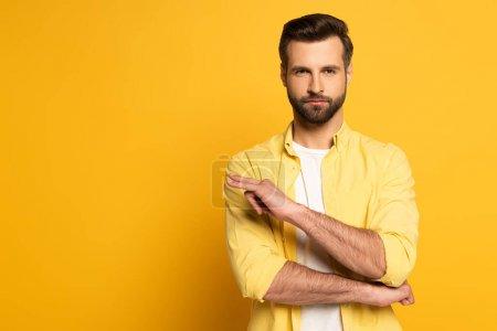 Photo pour Bel homme montrant geste dans un langage sourd et muet sur fond jaune - image libre de droit