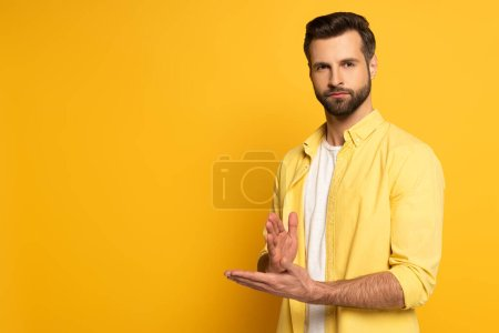 Young man looking at camera while showing gesture in deaf and dumb language on yellow background