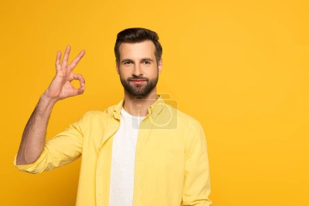 Handsome man looking at camera while showing okay gesture on yellow background