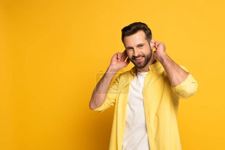 Photo pour Smiling man showing gesture in deaf and dumb language on yellow background - image libre de droit