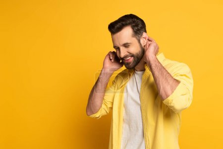 Photo pour Smiling man with closed eyes showing gesture in deaf and dumb language on yellow background - image libre de droit