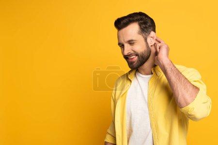 Photo pour Homme souriant avec les yeux fermés montrant le geste de langage sourd et muet sur fond jaune - image libre de droit
