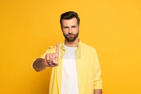 Photo pour Beau homme pointant du doigt sur fond jaune - image libre de droit