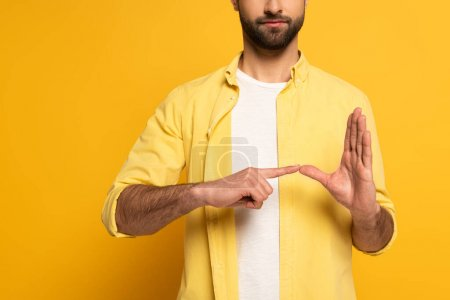 Cropped view of man showing gesture from sign language on yellow background