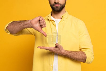 Cropped view of bearded man showing gesture in deaf and dumb language on yellow background