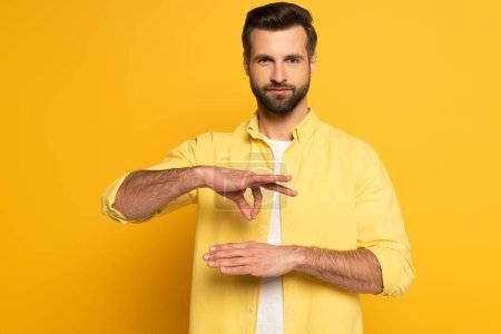 Man showing gesture in deaf and dumb language on yellow background