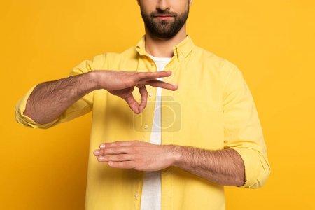 Photo pour Vue croustillante de gestes d'un homme en utilisant le langage gestuel sur fond jaune - image libre de droit
