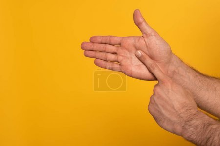 Cropped view of male hands showing gesture in deaf and dumb language isolated on yellow
