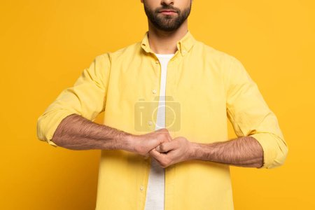 Photo for Cropped view of man showing cohesion sign in deaf and dumb language on yellow background - Royalty Free Image