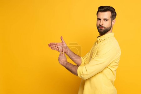 Photo for Side view of young man showing sign in deaf and dumb language on yellow background - Royalty Free Image