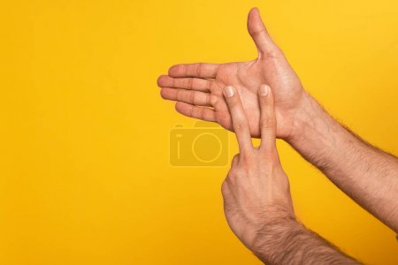 Photo pour Cropped view of man showing gesture in deaf and dumb language isolated on yellow - image libre de droit
