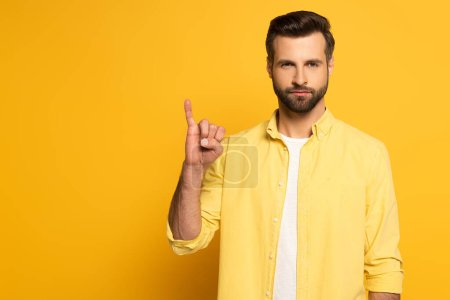 Handsome man showing letter in deaf and dumb language on yellow background