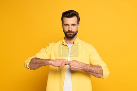 Man looking at camera while showing word friend in deaf and dumb language on yellow background