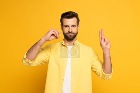 Photo for Handsome man showing letters in deaf and dumb language on yellow background - Royalty Free Image