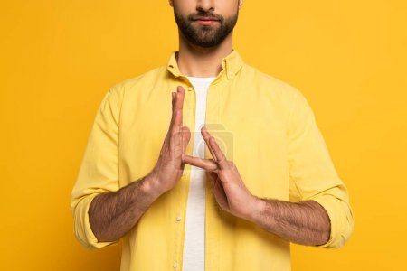 Photo pour Vue recadrée de l'homme montrant le signe dans un langage sourd et muet sur fond jaune - image libre de droit