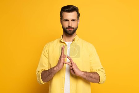Photo pour Bearded man showing sign in deaf and dumb language on yellow background - image libre de droit