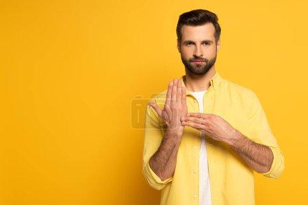 Photo pour Homme montrant un geste du langage des signes sur fond jaune - image libre de droit