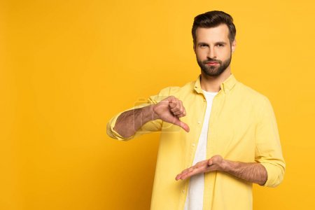 Man looking at camera while showing gesture from sign language on yellow background