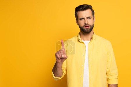 Photo pour Homme réfléchi pointant du doigt sur fond jaune - image libre de droit