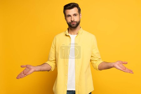 Photo for Handsome man showing shrug gesture on yellow background - Royalty Free Image
