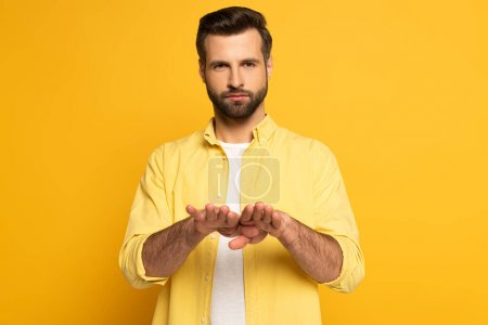 Young man using deaf and dumb language on yellow background
