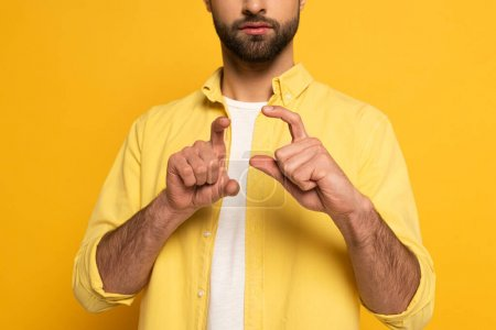 Cropped view of man showing sign in deaf and dumb language on yellow background