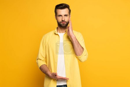 Man looking at camera while using gesture from sign language on yellow background