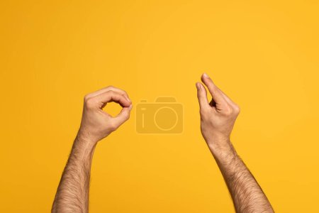 Cropped view of man using sign language isolated on yellow