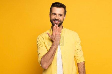 Photo pour Homme souriant regardant la caméra tout en montrant le mot parler en langue des signes sur fond jaune - image libre de droit