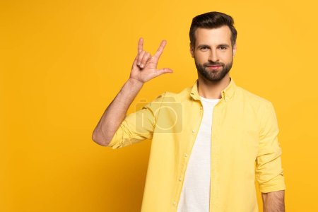 Handsome man showing word love in sign language on yellow background